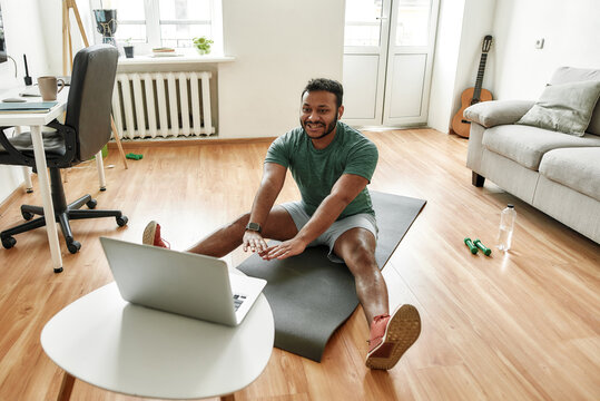 Cheerful stretching. Male fitness instructor showing exercises while streaming, broadcasting video lesson on training at home using laptop. Sport, online gym concept