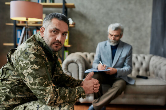 Get another vision. Middle aged military man looking aside during therapy session with psychologist. Soldier suffering from depression, psychological trauma. PTSD concept