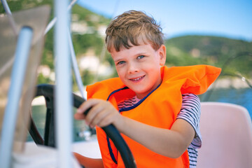 A cute kid learning to steer a boat