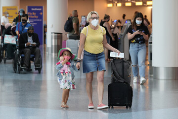 Passengers wear masks as they walk through LAX airport, as the global outbreak of the coronavirus disease (COVID-19) continues, in Los Angeles