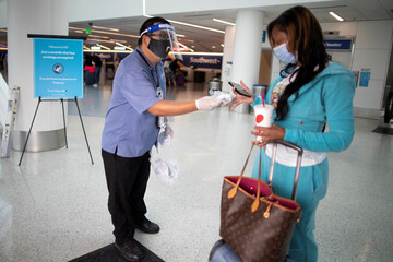 Travel Safely Ambassador Carlos Hernandez hands out a face masks to an airline passenger at LAX airport, as the global outbreak of the coronavirus disease (COVID-19) continues, in Los Angeles