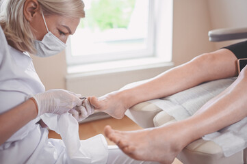 Professional medical pedicure procedure using nail clippers instrument. Patient visiting chiropodist podiatrist. Foot treatment in SPA salon. Podiatry clinic. Pedicurist hands in white gloves.