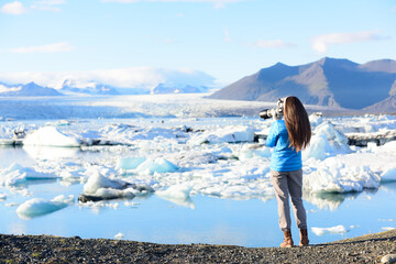 Photographer tourist woman taking photos with DSLR camera on travel on Iceland by Jokulsarlon glacial lagoon / glacier lake on Iceland. Happy tourist girl on travel in beautiful nature landscape.
