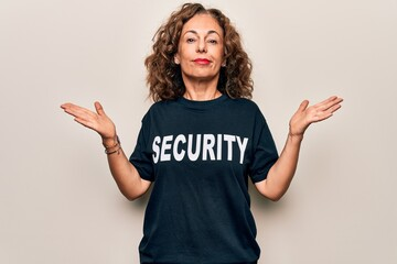Middle age beautiful guard woman wearing security t-shirt uniform over white background clueless...