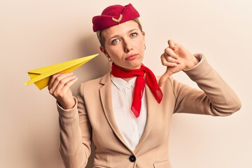 Young beautiful blonde girl wearing stewardess uniform holding paper plane with angry face, negative sign showing dislike with thumbs down, rejection concept