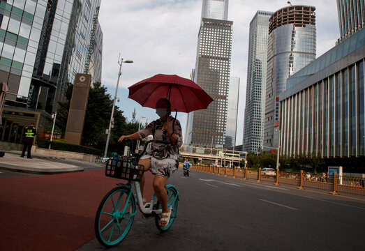 A woman holds an umbrella as she rides a Didi shared bicycle in the Central Business District in Beijing