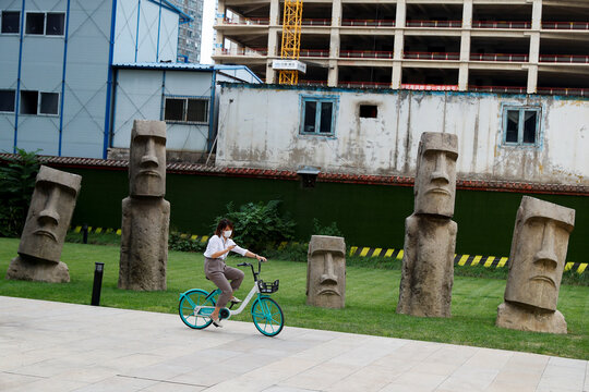 A woman sits on a Didi shared bicycle in front of Easter Island Moai replicas in the Central Business District in Beijing