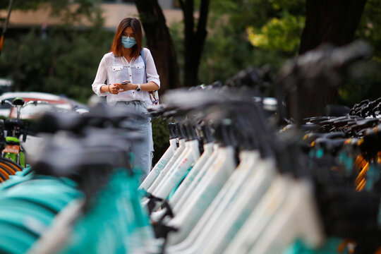A woman uses her phone to unlock a Didi shared bicycle in the Central Business District in Beijing