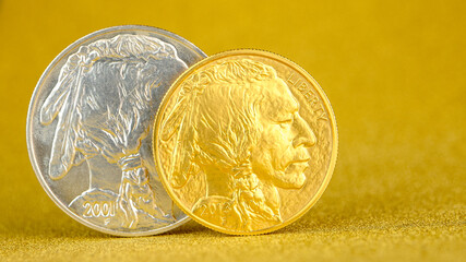 silver and golden american buffalo one ounce coins laying on silver and golden background.