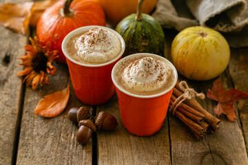 Pumpkin spiced latte in orange glasses on wood background, copy space