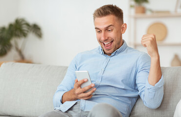Excited male employee feeling ecstatic holding phone