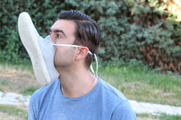 Man covering mouth and nose with shoe