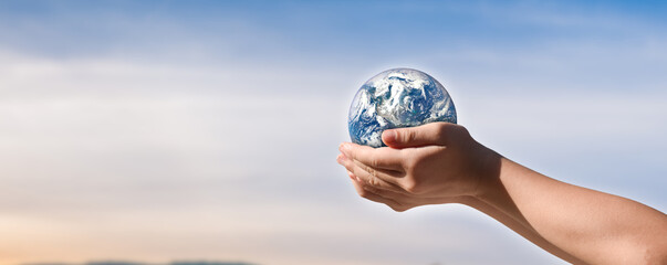 environment day concept, Globe in child hands over blue sky background. save of earth. Elements of this image furnished by NASA
