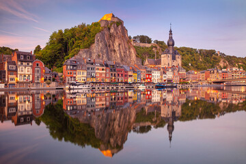 Fototapete - Dinant, Belgium. Cityscape image of beautiful historical city of Dinant with the reflection of the city in the Meuse River at summer sunset.