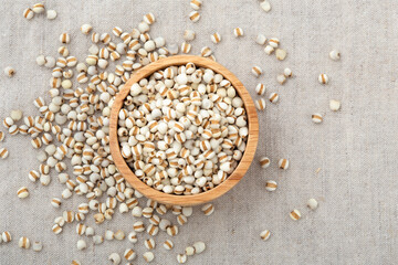 Pearl barley in wooden bowl on table