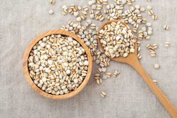 Pearl barley in wooden bowl with spoon
