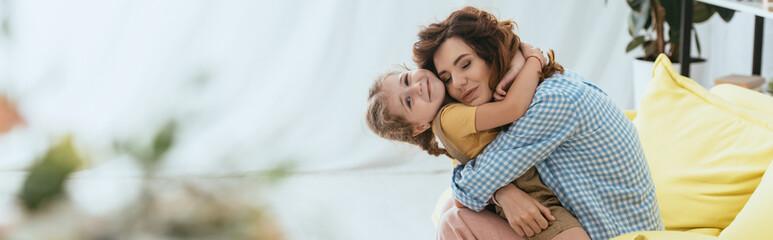 horizontal image of happy nanny hugging smiling kid while sitting on sofa