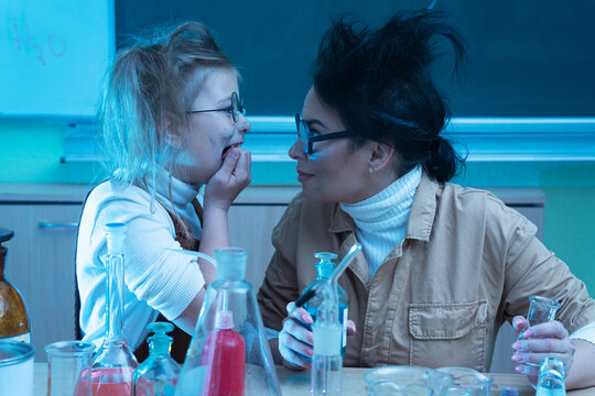 Teacher and little girl during chemistry lesson mixing chemicals in a laboratory