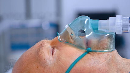 Close up of old man breathing with difficulties while wearing a respiratory oxygen mask....