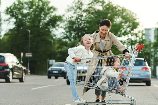Happy mother and her daughters are having fun with a shopping cart on a parking lot beside a supermarket.