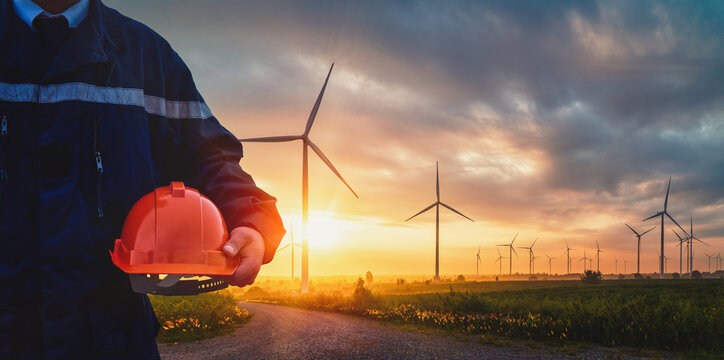 Technician Engineer in uniform and holding orange safety helmet with standing and checking wind turbine power farm Power Generator Station. Clean energy and environment
