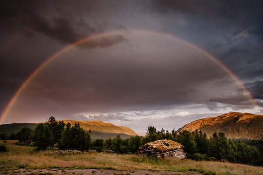 Scenic view of rainbow over mountains with hut in foreground