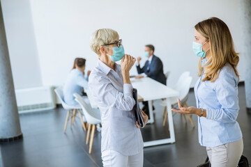 Two businesswomen talking in the office and wearing mask as a virus protection