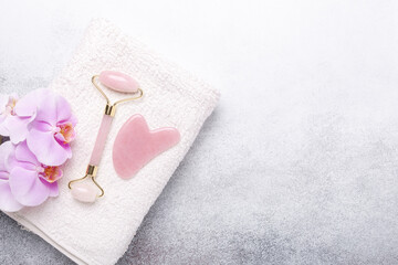 Rose Quartz jade roller and Gua Sha massager on towel on stone background. Massage tool for facial skin care, SPA beauty treatment concept