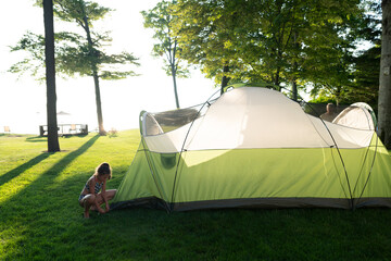 Young girl staking tent outside to go camping