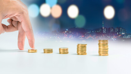 business and finance investment and saving activity with gold coin arrange and finger acting with soft focus night city background