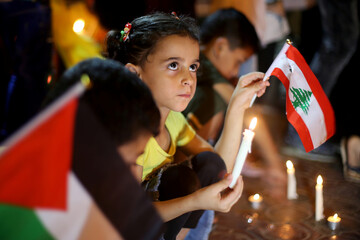 Palestinians light candles to show solidarity with the Lebanese people in Rafah