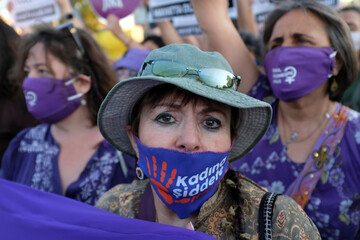 Demonstrators wearing protective masks take part in a protest against femicide and domestic violence, in Istanbul