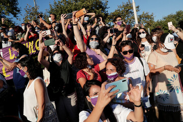 Demonstrators use their mobile phones to record a protest against femicide and domestic violence, in Istanbul