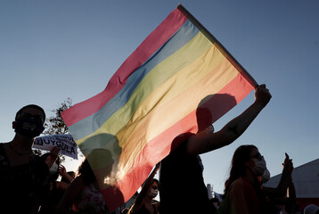 A demonstrator waves a rainbow flag during a protest against femicide and domestic violence, in Istanbul