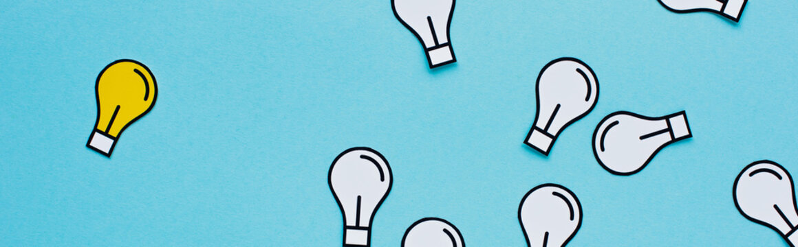 panoramic shot of paper light bulbs scattered on blue background, business concept