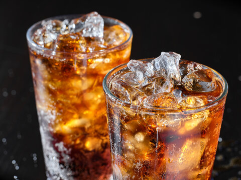 two cups of cold cola soft drink with ice