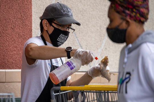 A grocery worker cleans shopping carts for arriving customers at a Food 4 Less store, during the outbreak of the coronavirus disease (COVID-19), in Los Angeles