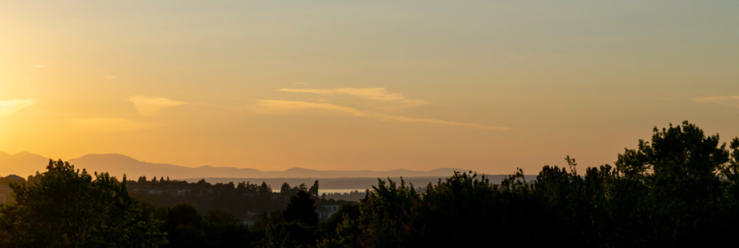 Wide panorama view of the Olympic Mountain Range in Washington State. The view of the Olympic mountain range is from the Capitol Hill district in Seattle during early evening hours.