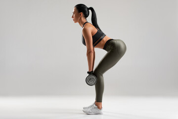 Fitness woman doing exercise for glutes on gray background. Athletic girl workout with dumbbells