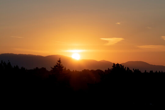 The sun sets behind the Olympic Mountains in Washington State. The view of the Olympic mountain range is from the Capitol Hill district in Seattle.