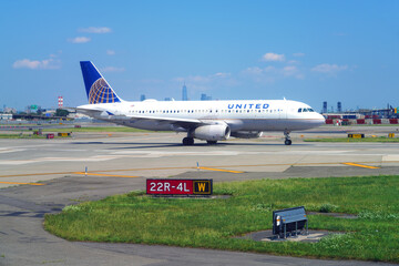 NEWARK, NJ -26 JUL 2020- View of an airplane from United Airlines (UA) at Newark Liberty International Airport (EWR) in New Jersey with the Manhattan New York skyline in the back.