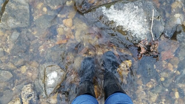 standing in a creek wearing rain boots