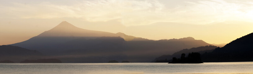 Panoramic shot of the gorgeous calm lake and mountains during sunset