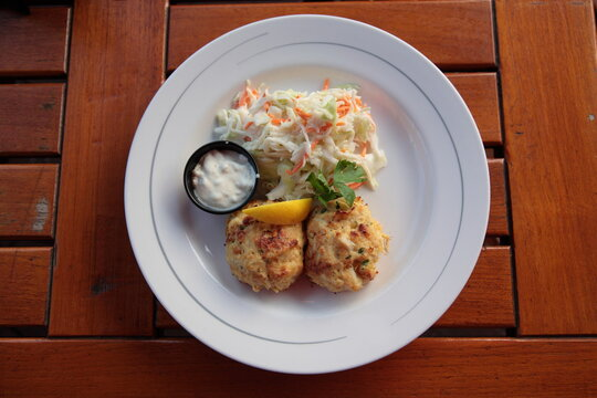 Close up of Typical Maryland Crab Cakes with salad and tartar sauce on table from a famous restaurant at inner harbor in Baltimore, USA