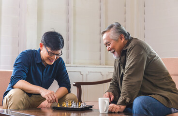 Senior asian father and middle aged son playing chess game in living room, Happiness Asian family...