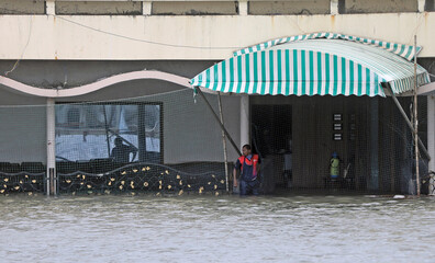 A man stands at the flooded entrance of a gymkhana after heavy rainfall in Mumbai