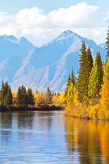 Beautiful autumn landscape with yellowed trees at the riverside and a mountain range on sunny afternoon. Siberia, Baikal region, Eastern Sayan Mountains,  Buryatia, Tunka foothill valley, Irkut River