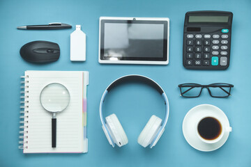 White wireless headphones, glasses, coffee and other objects on the blue background.