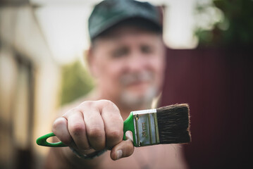 House painter is showing a paint brush in his hand close up.