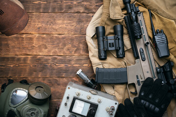 Rifle, gas mask, radio, binoculars and other equipment on the wooden table flat lay background with copy space.